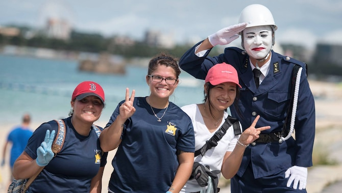 A cosplayed Mamoru-Kun renders a salute alongside members of Kadena Air Base and a local volunteer during a beach cleanup Oct. 9, 2016, at Araha Beach, Okinawa, Japan. Mamoru-Kun is an iconic figure from one of Okinawa's smaller islands, Miyako-Jima, who stands post as a lookout for society. (U.S. Air Force photo by Senior Airman Omari Bernard)