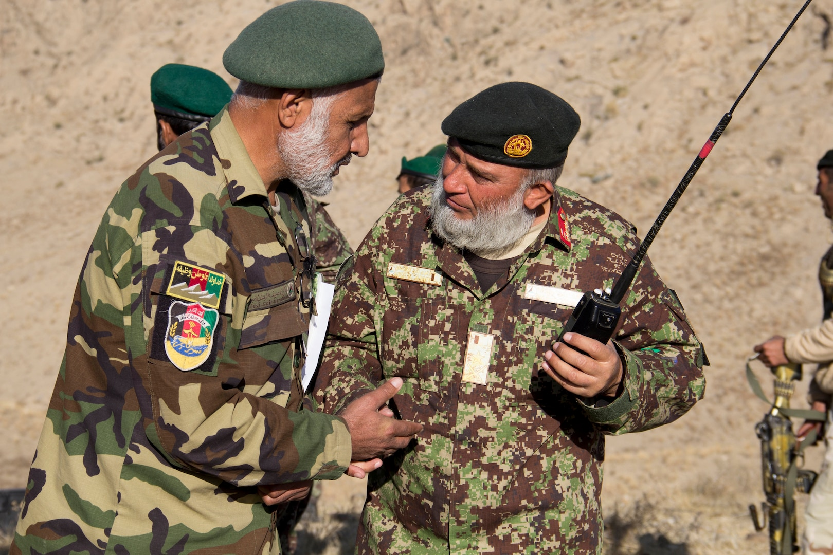 Two Afghan National Army officers with the 201st Corps discuss call for fire missions during a tolay attack battle drill near Camp Torah, Afghanistan, Dec. 27, 2016. The attack battle drill was conducted as part of the corps collective training cycle to build capability and capacity within the organization. (U.S. Army photo by Capt. Grace Geiger)