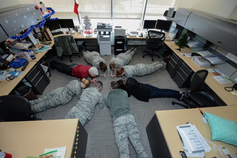 Members of the 55th Medical Group mental health section, perform planks during the work day at Offutt Air Force Base, Nebraska, Dec. 23, 2016 in the base clinic as a strategy to promote a culture of fitness in Airmen's daily lives. Members perform small exercises throughout the day instead of one intense workout to keep the body more active and healthy. (U.S. Air Force photo by Zachary Hada)