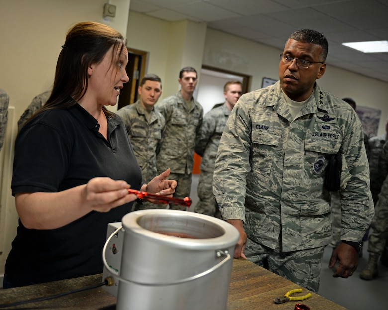 Mia Tobitt, 100th Maintenance Squadron isochronal inspection support section chief, demonstrates and explains a tool dipping innovation the 100th MXS implemented to U.S. Air Force Lt. Gen. Richard Clark, right, 3rd Air Force commander, during his visit Jan. 5, 2016, on RAF Mildenhall, England. Tools are dipped in a special, reusable plastic to prevent corrosion. This innovation saves 653 man hours and $35,000, a year. (U.S. Air Force photo by Senior Airman Christine Halan)