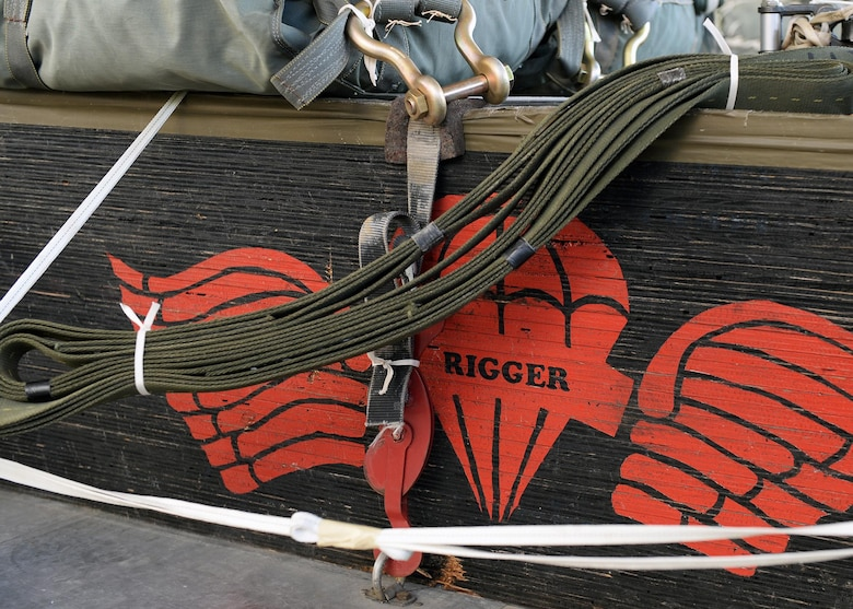 Aerial delivery specialists with the 86th Logistics Readiness Squadron's Rigging Barn, display their emblem on the side of an airdrop package at Ramstein Air Base, Germany, Dec. 29, 2016. Airmen who are certified riggers are the only persons able to inspect and certify a rigged package for drop. (U.S. Air Force photo by Senior Airman Jimmie D. Pike)