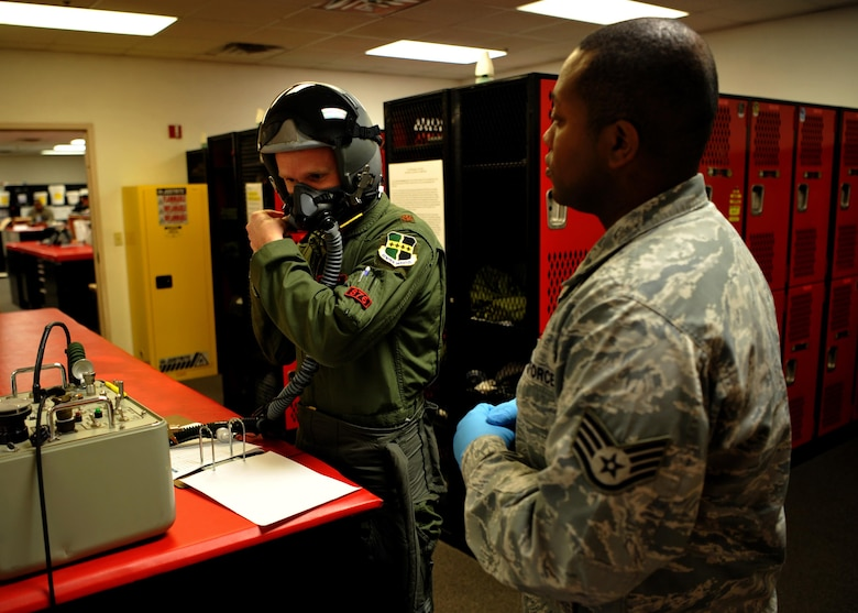 Maj. Matt Hellier (left), 1st Reconnaissance Squadron student pilot receives an equipment check from Staff Sgt. Matthew Young, 9th Operational Support Squadron noncommissioned officer in charge of aircrew flight equipment Jan. 5, 2016, at Beale Air Force Base, California. Aircrew flight equipment is responsible for all of a pilot's gear such as helmet, oxygen mask, harness and all life-saving devices. (U.S. Air Force photo/Staff Sgt. Jeffrey Schultze)