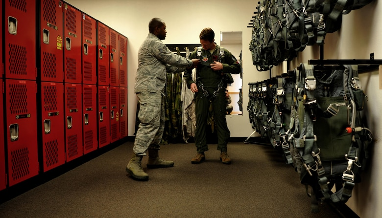 Maj. Matt Hellier (left), 1st Reconnaissance Squadron student pilot receives a parachute fitting from Staff Sgt. Matthew Young, 9th Operational Support Squadron noncommissioned officer in charge of aircrew flight equipment Jan. 5, 2016, at Beale Air Force Base, California. Aircrew flight equipment is responsible for all of a pilot's gear such as helmet, oxygen mask, harness and all life-saving devices. (U.S. Air Force photo/Staff Sgt. Jeffrey Schultze)