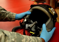 Staff Sgt. Matthew Young, 9th Operational Support Squadron noncommissioned officer in charge of aircrew flight equipment performs an equipment check on a pilot helmet Jan. 5, 2016, at Beale Air Force Base, California. Aircrew flight equipment personnel manage the inspection, maintenance and adjustments to the devices assigned to the pilots they support. (U.S. Air Force photo/Staff Sgt. Jeffrey Schultze)