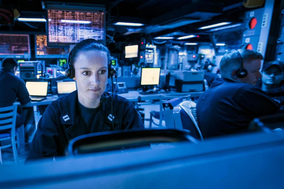 A sailor looks at the regional air and surface picture in a ship's command center.