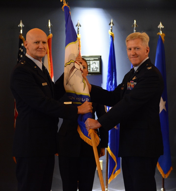Col. Brian K. Johnson, former 101st Air and Space Operations Group commander, passes the ceremonial flag to Brig. Gen. Jim Eifert, Florida Air National Guard commander, during the change of command ceremony at Tyndall Air Force Base, Florida Jan. 5. The passing of the flag symbolizes Johnson's passing of command.