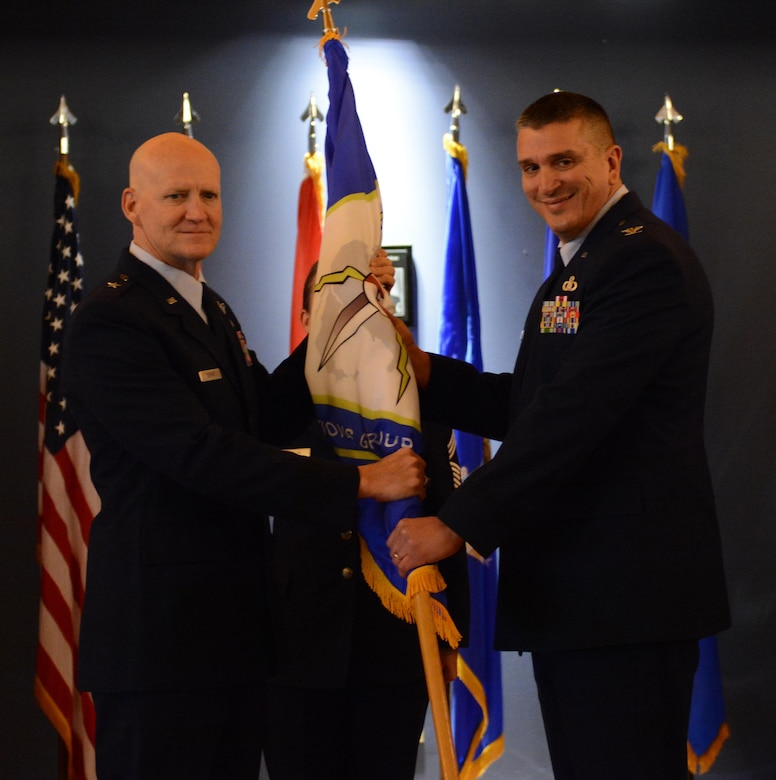 Col. Michael A Valle, 601st Air Operations Center Combat Operations Division chief, takes the ceremonial flag from Brig. Gen. Jim Eifert, Florida Air National Guard commander, during the 101st Air and Space Operations Group change of command ceremony on Tyndall Air Force Base, Florida Jan. 5. The passing of the flag symbolizes Valle's acceptance of command of the 101st AOG.