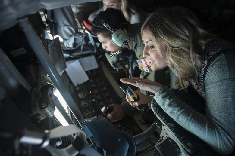 Emily Hagemeier, Team Shaw spouse, blows a kiss to her husband, Capt. Derek Hagemeier, 77th Fighter Squadron F-16CM Fighting Falcon pilot, during a collaborative refueling training and spouse flight event over the Atlantic Ocean, Dec. 21, 2016. Several Team Shaw spouses had the opportunity to watch from the aircraft's rear window as their husbands approached the KC-135 Stratotanker, which was assigned to the 93rd Air Refueling Squadron from Farichild Air Force Base, Wash., to practice refueling procedures. (U.S. Air Force photo by Senior Airman Zade Vadnais)