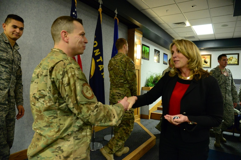 Secretary of the Air Force Honorable Deborah Lee James coins Master Sgt. Cory La Salle, 741st Missile Security Forces Squadron convoy response force section chief, at Malmstrom Air Force Base, Mont., Jan. 5, 2017. During her visit, James discussed improvements in morale, innovation and modernization with enlisted Airmen from all squadrons and ranks to gain a better understanding on what areas and processes still need to be evaluated for positive change or more effective mission accomplishment from a tactical perspective. (U.S. Air Force photo/Airman 1st Class Magen M. Reeves)