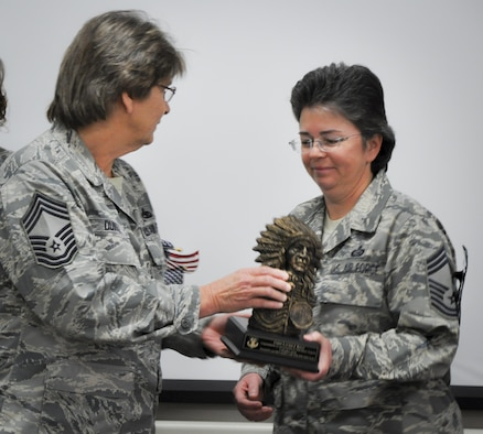Chief Master Sgt. Pamela Duvall, 919th Special Operations Maintenance Group, presents a Native American chief bust to newly promoted Chief Master Sgt. Laurie Kent, 919th Special Operations Force Support Squadron, at her Chief Induction ceremony Jan. 7 at Duke Field, Fla.  Kent was promoted to chief via the Stripes for Exceptional Performers II program in August.  (U.S. Air Force photo/Lt. Col. James Wilson)