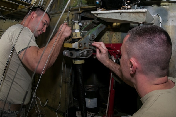 """Tech Sgt. Trevor Gray and Master Sgt. Jared Richmond, 434th Maintenance Group repair and reclamation technicians, reinstall a stabilizer trim actuator on Jan. 8, 2017 at Grissom Air Reserve Base, Ind. The actuator is located in a small compartment in the tail of the aircraft often referred to as the """"hellhole."""" (U.S. Air Force photo/Staff Sgt. Dakota Bergl)"""