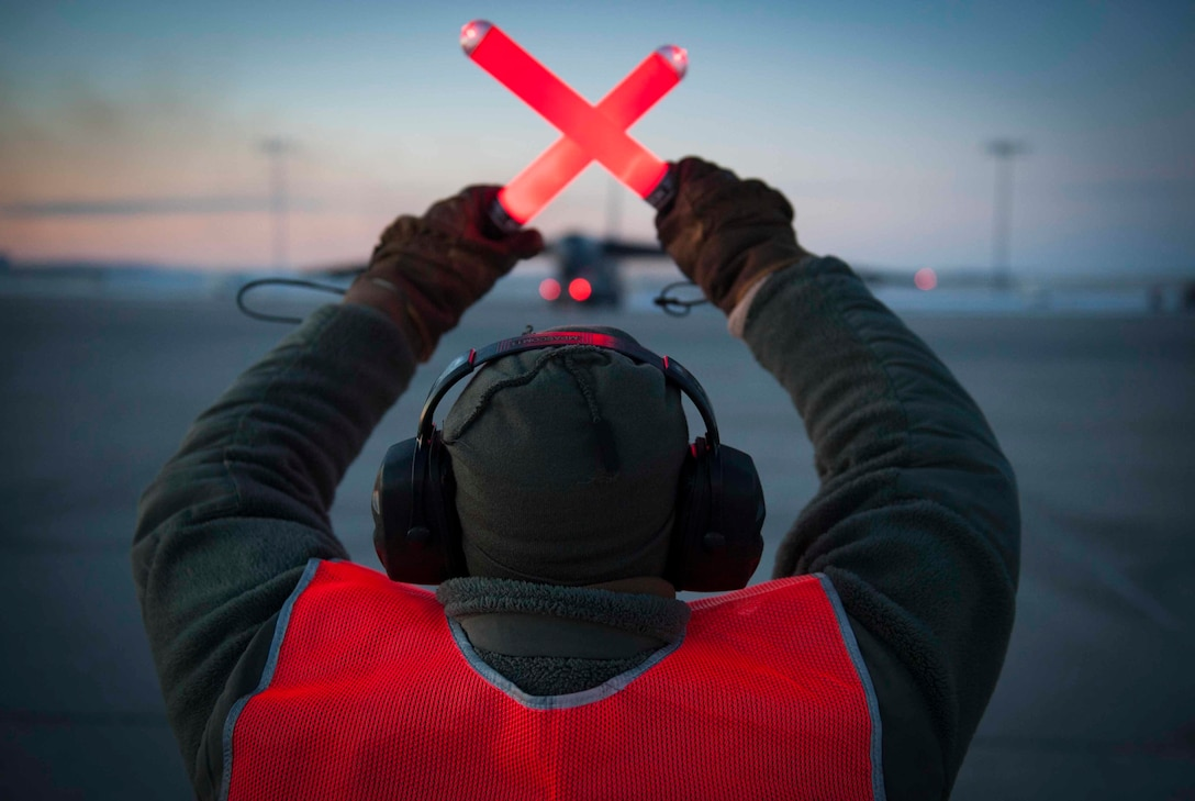 Senior Airman Taylor Lancaster, a 5th Aircraft Maintenance Squadron aircraft crew chief, guides a B-52H Stratofortress on Minot Air Force Base, N.D., Jan. 9, 2015. Lancaster's main duty is to ensure his jet is fixed and prepared to take off before its flight time. (U.S. Air Force photo/Airman 1st Class Sahara L. Fales)