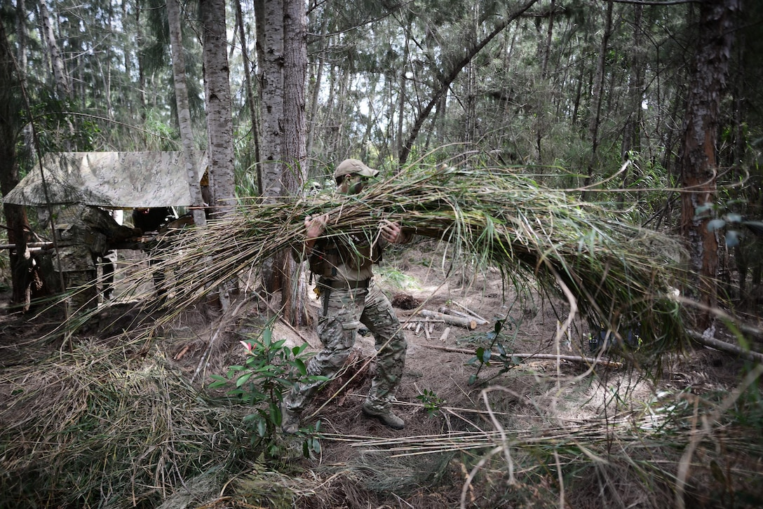 Senior Airman Ian Kuhn, a survival, evasion, resistance and escape instructor with the 103rd Rescue Squadron, demonstrates how to build a concealed shelter during a combat and water survival training course Jan. 20, 2016, at Homestead Air Reserve Base, Fla. During this course, aircrew members gained refresher training on using their emergency radios, tactical movements through difficult terrain, how to build shelters, ways to build fires and methods for evading the enemy. (U.S. Air National Guard/Staff Sgt. Christopher S. Muncy)
