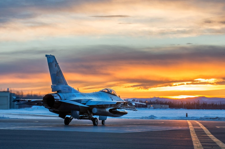 An F-16 Fighting Falcon with the 18th Aggressor Squadron prepares to take off from Eielson Air Force Base, Alaska, shortly after sunrise Jan. 24, 2016, in transit to Kadena Air Base, Japan, to participate in training exercises. More than 150 maintainers from the 354th Fighter Wing will keep the aggressors in the air and prepare Airmen, Sailors and Marines for contingency operations along with coalition partners in the Pacific theater. (U.S. Air Force photo/Staff Sgt. Shawn Nickel)