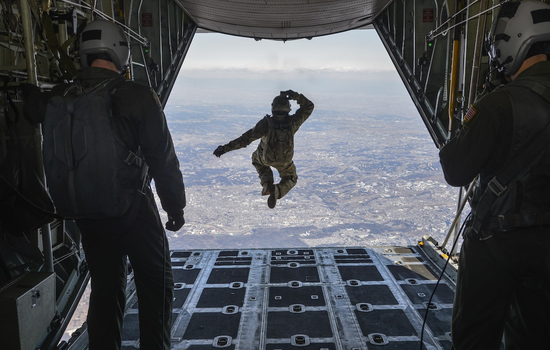 Tech. Sgt. Benjamin Jonas, the 374th Operations Support Squadron's survival, evasion, resistance and escape operations NCO in charge, jumps out of a C-130 Hercules while flying over Yokota Air Base, Japan, March 2, 2016. During the high-altitude, low-opening airdrop, Jonas jumped from 10,000 feet and parachuted to the base. (U.S. Air Force photo/Senior Airman David Owsianka)