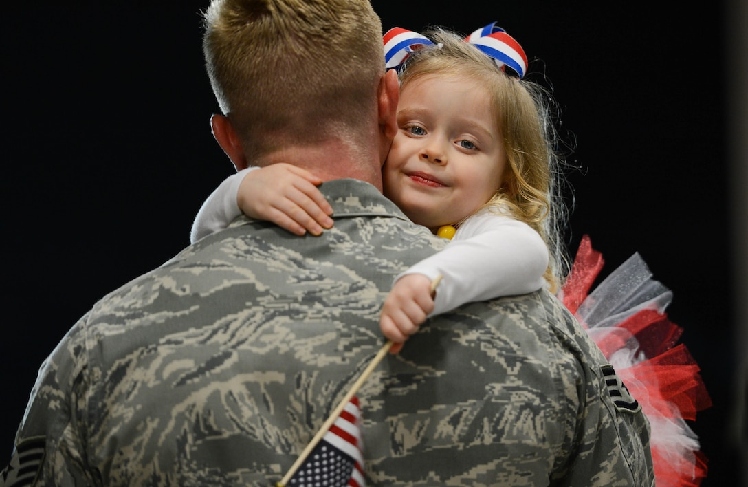 An Airman assigned to the 20th Fighter Wing is embraced by his daughter after returning to Shaw Air Force Base, S.C., April 13, 2016. Approximately 300 Airmen deployed for six months to the U.S. Central Command area of responsibility. (U.S. Air Force photo/Senior Airman Jensen Stidham)