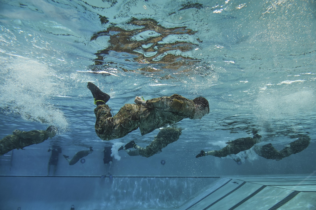 Special Tactics Training Squadron students swim the length of the pool with their hands and feet bound during a pre-scuba class at Hurlburt Field, Fla., June 29, 2016. The training familiarizes trainees with the basics of water operations. Trainees perform tasks such as tying knots underwater, staying afloat without their arms and hands, and using snorkeling gear. (U.S. Air Force photo/Senior Airman Ryan Conroy)
