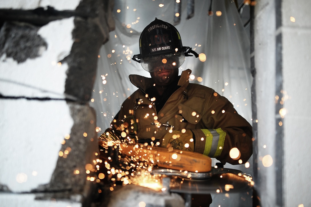 Staff Sgt. Daniel Glenn, a firefighter with the 106th Rescue Wing, operates a powered saw to cut through a reinforced cinder block wall at Francis S. Gabreski Air National Guard Base, N.Y., Aug. 25, 2016. (U.S. Air National Guard photo/Staff Sgt. Christopher S. Muncy)