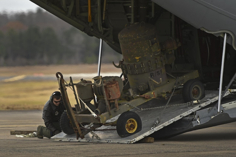 U.S. Air Force Staff Sgt. Casey Strauss, 61st Airlift Squadron C-130J loadmaster, simulates a Method A Combat Offload of a fuel filter separator during a deployment training exercise Dec 7, 2016 at Little Rock Air Force Base, Ark. Method A Combat Offloads are often utilized in locations where there are no vehicles or equipment to assist in offloading supplies. (U.S Air Force photo by Senior Airman Harry Brexel)
