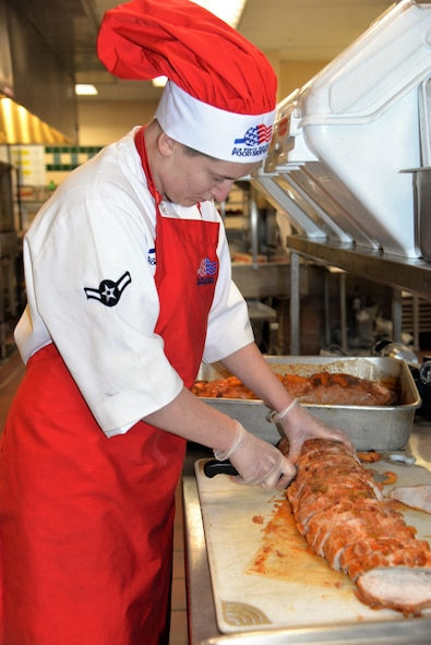 Airman Candace Ellenburg, 90th Force Support Squadron food services apprentice, prepares for lunch in Chadwell dining facility at F. E. Warren Air Force Base, Wyo., Dec. 17, 2016. Ellenburg is an eager food service Amn always willing to lend a hand and improve her culinary skills. (U.S. Air Force phot by 2nd Lt. Nikita Thorpe)