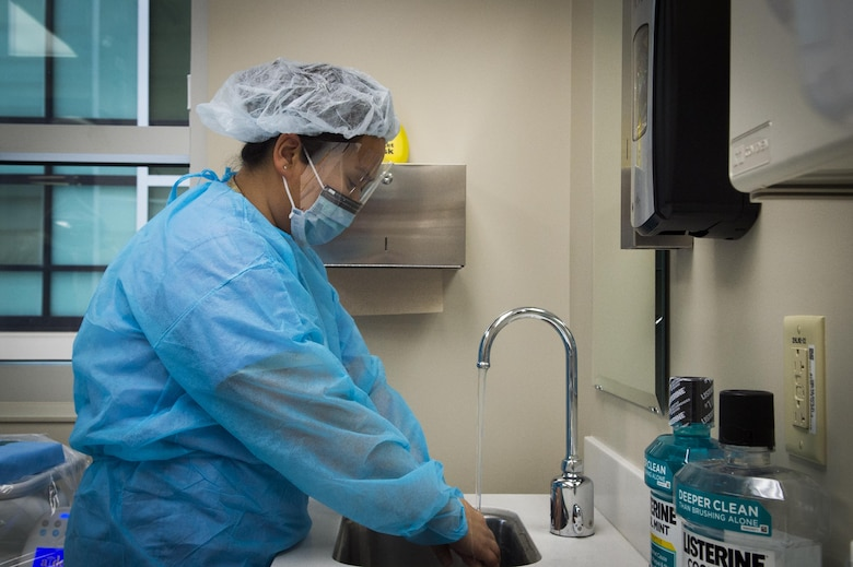 Master Sgt. Millicent Cavazos, 779th Medical Group dental squadron dental hygienist, washes her hands while preparing to perform a dental cleaning at Joint Base Andrews, Md., Jan. 6, 2017. The dental clinic now sees patients in the new edition to Malcolm Grow Medical Clinics and Surgery Center as well as their former clinic to maximize efficiency for patients. (U.S. Air Force photo by Senior Airman Mariah Haddenham)