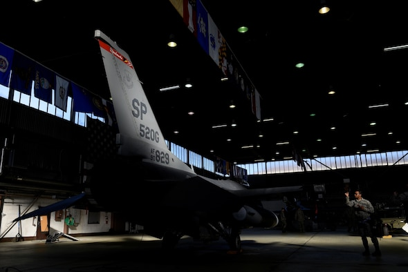 U.S. Air Force Airman 1st Class Licinio Monteiro, 52nd Aircraft Maintenance Squadron weapons load crew member, prepares an F-16 Fighting Falcon for inert weapons to be loaded during the quarterly weapons load competition in Hangar One at Spangdahlem Air Base, Germany, Jan. 6, 2017. The competition consisted of two teams competing against each other to load weapons quickly and accurately. (U.S. Air Force photo by Staff Sgt. Jonathan Snyder)