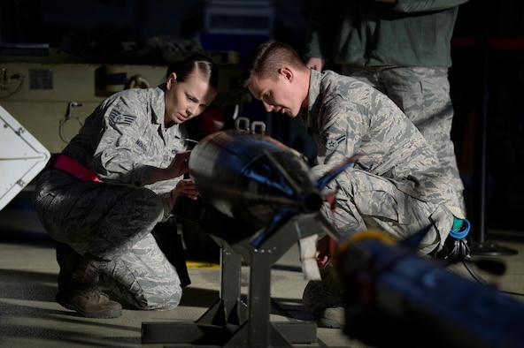 U.S. Air Force Staff Sgt. Sarah Gonzales, left, 52nd Aircraft Maintenance Squadron weapons load crew chief, and Airman 1st Class Joshua Reeves, right, 52nd AMXS weapons load crew member, prepares an inert weapon to be loaded on an F-16 Fighting Falcon during the quarterly weapons load competition in Hangar One at Spangdahlem Air Base, Germany, Jan. 6, 2017. The competition consisted of two teams competing against each other to load weapons quickly and accurately. (U.S. Air Force photo by Staff Sgt. Jonathan Snyder)