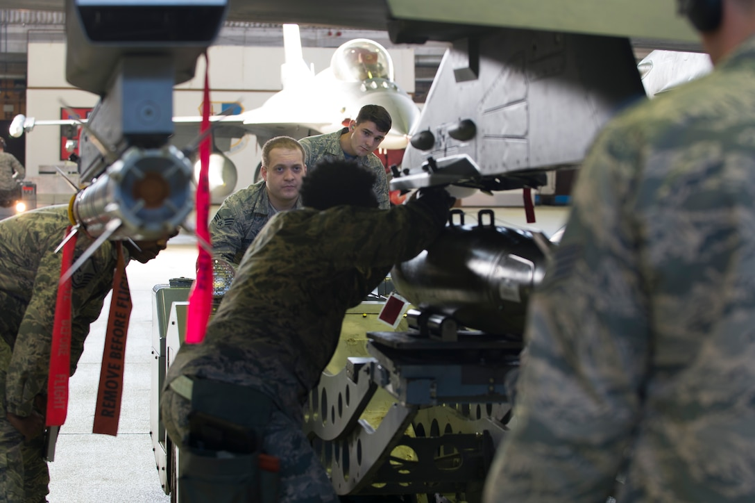 52nd Fighter Wing evaluators observe Staff Sgt. DeAnte Miller and Senior Airman Michael Curtis, both 52nd Aircraft Maintenance Squadron tactical aircraft weapons systems specialists, during the 52nd FW Load Crew of the Quarter competition at Spangdahlem Air Base, Germany, Jan. 6, 2017. Family, friends and members of the Spangdahlem community attended the competition to see which of the two teams of three maintenance Airmen would move on to the annual load competition. (U.S. Air Force photo by Senior Airman Dawn M. Weber)