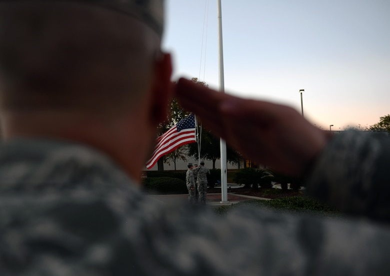 Airmen from the 81st Training Group lower the U.S. flag during a retreat ceremony at the Levitow Training Support Facility, Dec. 15, 2016, on Keesler Air Force Base, Miss. Students from the 81st Training Support Squadron Military Training Leader Course attended retreat as part of the four-week course's more robust hands-on time with non-prior service Airmen. (U.S. Air Force photo by Senior Airman Duncan McElroy)