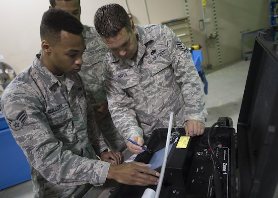Senior Airman Devon Guillory and Tech. Sgt. Adam Hayes, 49th Maintenance Squadron aircraft structural maintenance technicians, analyze readings on a hot bonder, Dec. 14, 2016, at Holloman Air Force Base, N.M. The hot bonder adjusts the temperature for vacuum repairs on composite structures. Once the composite structure is repaired, it can be sanded, painted and returned to the aircraft. (U.S. Air Force photo by Senior Airman Emily Kenney)