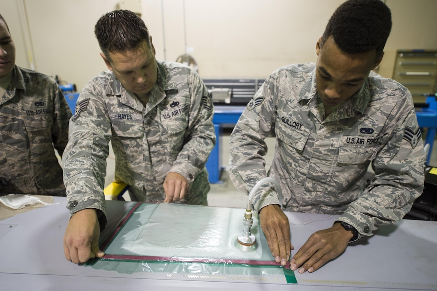 Senior Airman Devon Guillory and Tech. Sgt. Adam Hayes, 49th Maintenance Squadron aircraft structural maintenance technicians, create a seal on a vacuum repair on a composite structure, Dec. 14, 2016, at Holloman Air Force Base, N.M. Once the composite structure is repaired, it can be sanded, painted and returned to the aircraft. (U.S. Air Force photo by Senior Airman Emily Kenney)