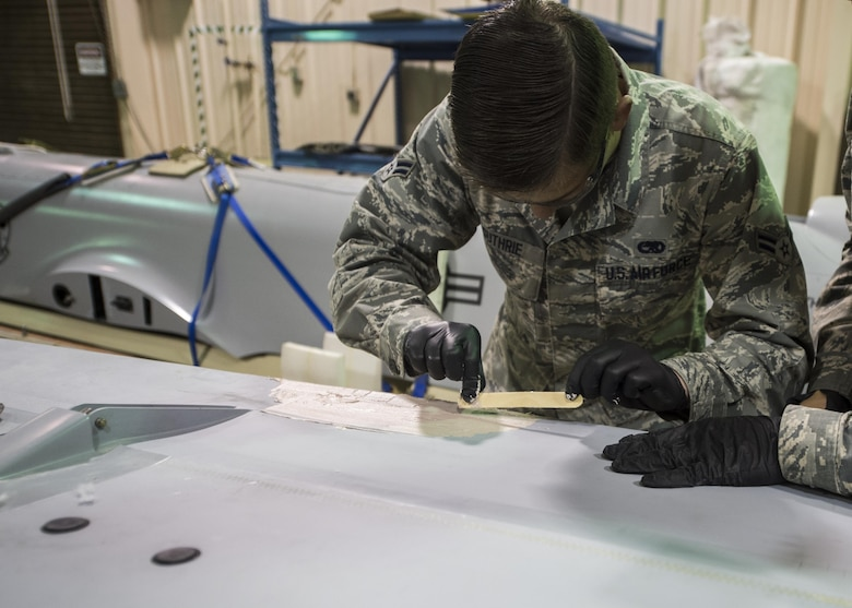 Airman 1st Class Joshua Guthrie, a 49th Maintenance Squadron aircraft structural maintenance technician, applies aircraft smoothing compound to an MQ-1 Predator wing, Dec. 14, 2016, at Holloman Air Force Base, N.M. The sheet metal shop has been prepping an MQ-1 Predator static display for Heritage Park, pending the Predator's retirement in early 2017. (U.S. Air Force photo by Senior Airman Emily Kenney)
