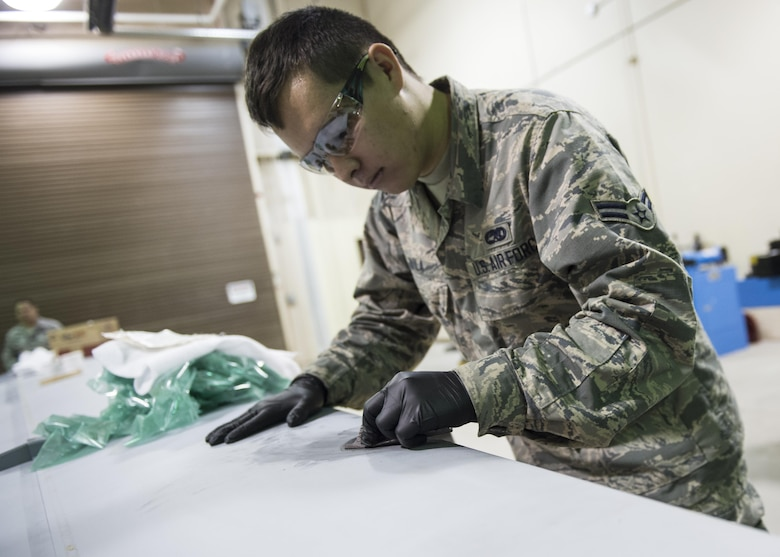 Airman 1st Class Nathaniel Avila, a 49th Maintenance Squadron aircraft structural maintenance technician, sands down a composite structural repair, Dec. 14, 2016, at Holloman Air Force Base, N.M. Structural maintenance technicians primarily do back shop repairs and flight line jobs for both F-16 Fighting Falcons and MQ-9 Reapers. They also re-manufacture parts that are no longer available for purchase. (U.S. Air Force photo by Senior Airman Emily Kenney)