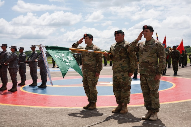 """U.S. Army 7th Special Forces Group (Airborne) Soldiers present their unit's guidon December 7, 2016 during an award ceremony in Florencia, Colombia. A Colombian Army Counter-narcotics Brigade, known as BRCNA, honored the U.S. Special Forces unit with the unit's """"Bandera de Guerra"""" military medal. (U.S. Army photo by Staff Sgt. Osvaldo Equite)"""