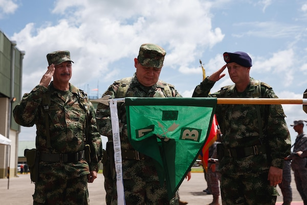 "Colombian army Col. Walther G. Jimenez, right, salutes as a Colombian general officer places the ""Bandera de Guerra"" military medal onto the U.S. Army's B. Co., 3rd Bn., 7th Special Forces Group's guidon December 7, 2016 during a ceremony in Florencia, Colombia. Jimenez is Colombia's National Army Counter-narcotics Brigade commander. (U.S. Army photo by Staff Sgt. Osvaldo Equite)"