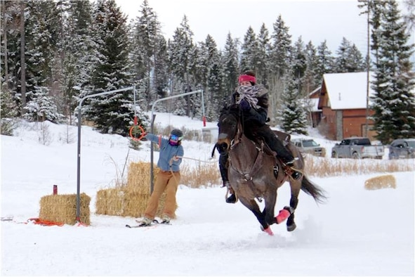 Air Force Office of Special Investigations Special Agent Katherine Licht and her horse, Storm, go Skijoring with a skier in Montana. Skijoring is like waterskiing behind a horse and is a winter outdoor equestrian sport in the western state. (Courtesy photo/SA Katherine Licht)