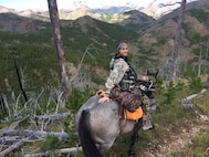 Air Force Office of Special Investigations Special Agent Katherine Licht, and her horse Storm, pause during a bow hunting trip in Montana's rugged terrain. (Courtesy photo/SA Katherine Licht)