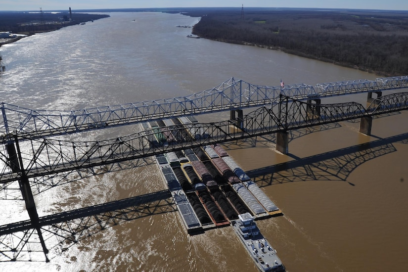 A tug pushing 35 barges makes its way past oil removal operations near mile marker 436 on the Mississippi River, Jan. 31, 2013. More than 60 vessels and 900 barges have been cleared through the safety zone between mile marker 425 and mile marker 441. Coast Guard photo by Petty Officer 3rd Class Jonathan Lally.