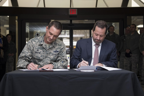 Col. Ethan Griffin, 436th Airlift Wing commander, and John Sisson, Delaware Transit Corporation CEO, sign memorandums of understanding Jan. 5, 2017, at Eagle's Rest Inn on Dover Air Force Base, Del. The MOU commemorated the partnership that culminated in a new bus route extending onto the installation. (U.S. Air Force photo by Senior Airman Aaron J. Jenne)