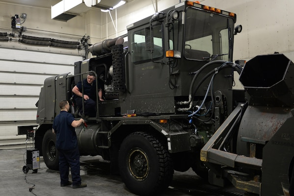 U.S. Air Force Staff Sgt. Robert Sommerfeldt and Senior Airman Dakota Greenwade, both 354th Logistics Readiness Squadron vehicle maintenance technicians, work together to pinpoint the issue with a snow blower at Eielson Air Force Base, Jan. 6, 2017.  Sommerfeldt and Greenwade ran tests on the machine to best diagnose the problem and fix it.