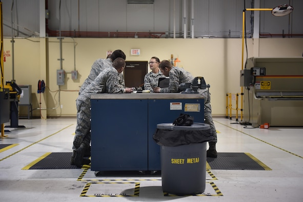 Aircraft Structural Maintenance apprentices with the 27th Special Operations Maintenance Squadron discuss a repair with Tech. Sgt. Matthew Foster, 27th Special Operations Maintenance Squadron Aircraft Structural Maintenance supervisor, November 16, 2016 at Cannon Air Force Base, N.M. Sheet metals technicians are part of a large group of Cannon Air Commandos who work through the night to keep aircraft flying. (U.S. Air Force Photo by Senior Airman Shelby Kay-Fantozzi/released)