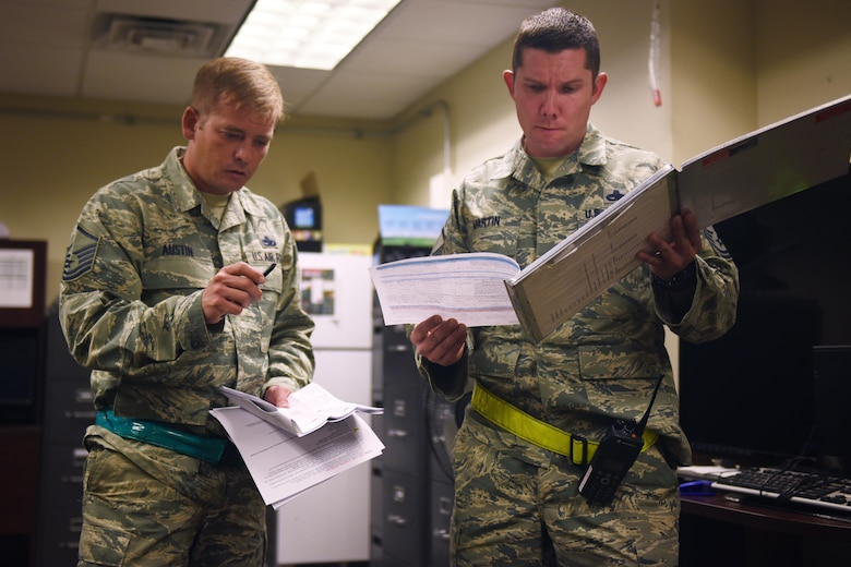 U.S. Air Force Master Sgts. Gabriel Austin, 27th Special Operations Aircraft Maintenance Squadron CV-22 production superintendent, and Christian Martin, 27th Special Operations Maintenance Squadron production superintendent, coordinate a full night's to-do list November 16, 2016 at Cannon Air Force Base, N.M. Production superintendents task out the night's repairs and bridge between the multiple shops working through the night to get the job done. (U.S. Air Force Photo by Senior Airman Shelby Kay-Fantozzi/released)