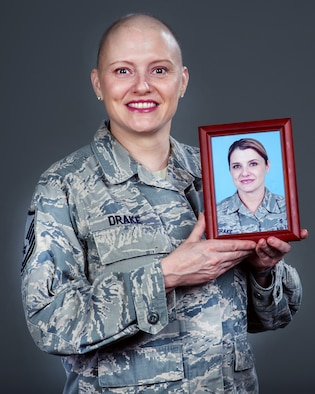 U.S. Air Force Master Sgt. Tracey Drake, 60th Medical Operations Squadron poses with a picture of herself prior to losing her hair from chemotherapy treatment, Travis Air Force Base, Calif., Dec. 15, 2016. Drake was diagnosed with metastatic breast cancer during her retirement physical in July 2016, 3 weeks before starting terminal leave. Drake faces more chemotherapy, surgery, radiation, targeted infusion, and reconstruction surgery. (U.S. Air Force photo/Louis Briscese)