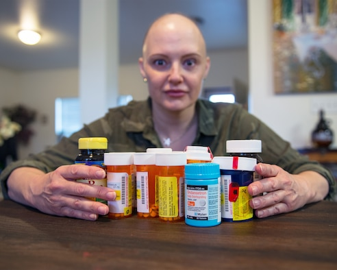 U.S. Air Force Master Sgt. Tracey Drake, 60th Medical Operations Squadron poses with her required medications, Travis Air Force Base, Calif., Jan. 10, 2017. Drake was diagnosed with metastatic breast cancer during her retirement physical in July 2016, 3 weeks before starting terminal leave. Drake faces surgery, radiation, targeted infusion, and reconstruction surgery. (U.S. Air Force photo/Louis Briscese)