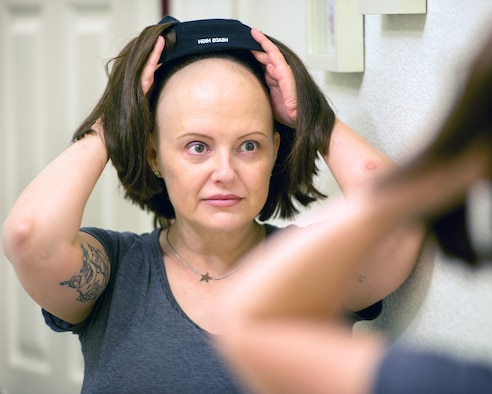 U.S. Air Force Master Sgt. Tracey Drake, 60th Medical Operations tries on a wig, Travis Air Force Base, Calif., Jan. 10, 2017. Drake was diagnosed with metastatic breast cancer during her retirement physical in July 2016, 3 weeks before starting terminal leave. Drake faces surgery, radiation, targeted infusion, and reconstruction surgery. (U.S. Air Force photo/Louis Briscese)