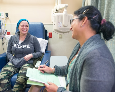 U.S. Air Force Master Sgt. Tracey Drake, 60th Medical Operations Squadron and Dr. Sareena Malhi, Hematology & Medical Oncology, enjoy a laugh before Drake is administered her chemotherapy treatment, Travis Air Force Base, Calif., Dec. 13, 2016. Drake was diagnosed with metastatic breast cancer during her retirement physical in July 2016, 3 weeks before starting terminal leave. Drake faces more chemotherapy, surgery, radiation, targeted infusion, and reconstruction surgery. (U.S. Air Force photo/Louis Briscese)