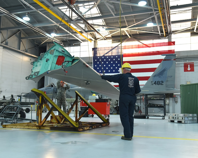 Members of the 142nd Fighter Wing and the Depot Field Team from the 402nd Aircraft Maintenance Group, Robins Air Force Base, Ga., lift a new wing to be placed on an F-15C Eagle assigned to the 142nd Fighter Wing, Portland Air National Guard Base, Ore., Dec. 6, 2016. (U.S. Air National Guard photo by Senior Master Sgt. Shelly Davison, 142nd Fighter Wing Public Affairs)