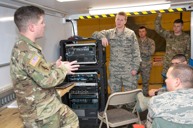 U.S. Army Staff Sgt. Michael Copen, left, a computer network technician for West Virginia National Guard Joint Force Headquarters, discusses the Joint Incident Site Communication Capability kit with U.S. Air Force Senior Airman Trevor Whittington, standing, a system administrator for the 167th Airlift Wing. JFHQ-WV signed over the JISCC to the 167th Communications Flight in December. The satellite-based communication system provides internet, telephone and radio capabilities during emergency events where normal communications may be disabled. (U.S. Air National Guard photo by Senior Master Sgt. Emily Beightol-Deyerle)