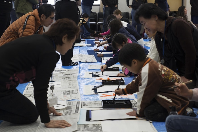 Children from Marine Corps Air Station Iwakuni and Japanese local children practice calligraphy with the help of instructors in Waki Town, Japan, Jan. 7, 2017.  The children learned how to write their goals in Kanji for the new year. Similar to the American tradition of New Year's resolutions, the Japanese use calligraphy to write their goals at the beginning of every new year.   (U.S. Marine Corps photo by Lance Cpl. Joseph Abrego)