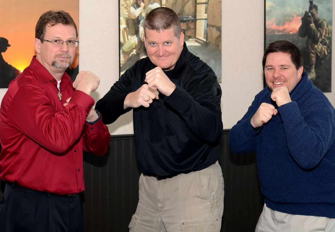 Mike Griffith, Joseph Coslett and Bryan Gatewood, board members of Gold in Fight, a charity that aims to help families overcome the stresses that come from dealing with childhood cancer, put up their dukes Jan. 10, 2017, at the Defense Information School on Fort Meade, Md. Griffith, left, is the school's director of logistics; Coslett, center, is an academic director in the public affairs leadership department; and Gatewood is an instructor whose daughter has been cancer-free for six years.
